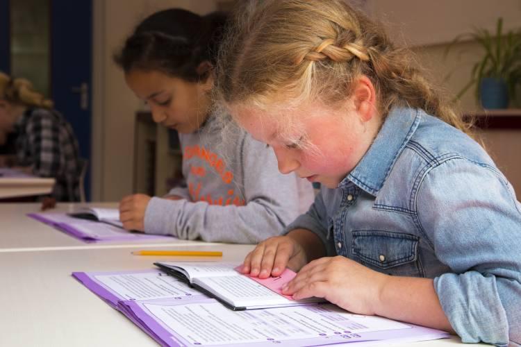 twee meisjes lezen op school