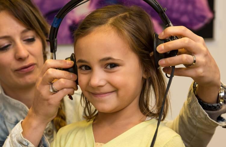 Meisje krijgt van onderzoekster hoofdtelefoon opgezet