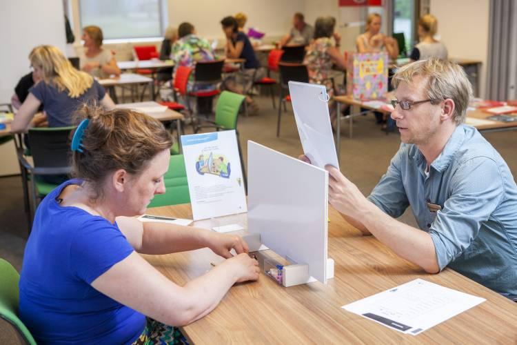 Man en vrouw zitten aan tafel met tussenschot tussen hen in en communiceren met elkaar