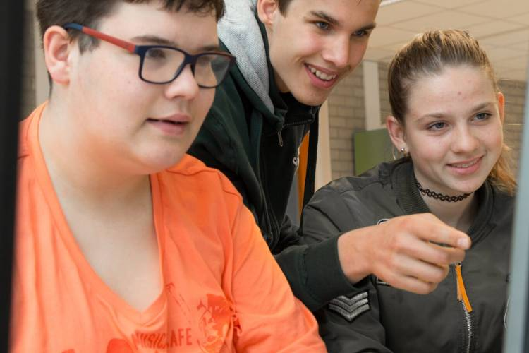 Drie jongeren lezen van een beeldscherm