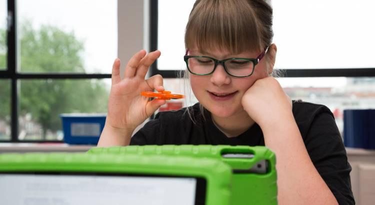 Meisje met spinner in haar hand kijkt op iPad scherm