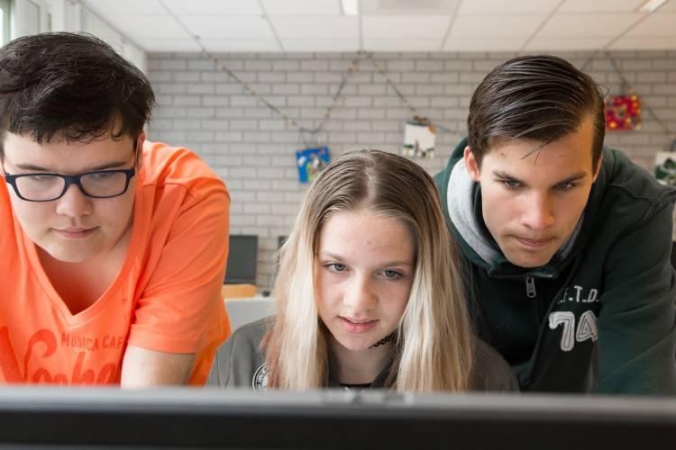 Drie jongeren buigen zich naar een beeldscherm om te lezen