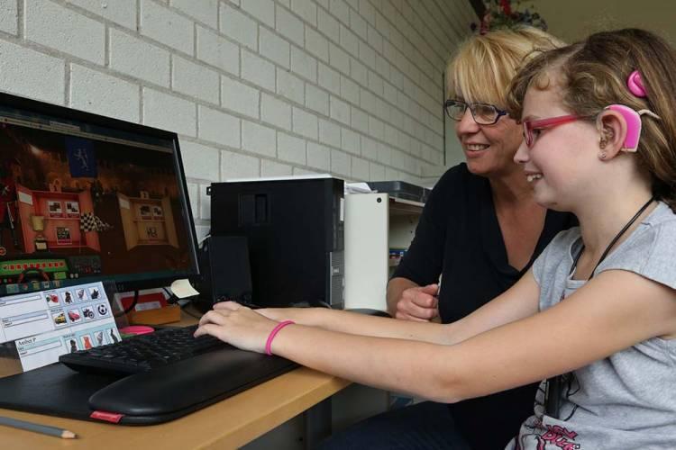 Leerkracht en meisje met CI voor beeldscherm met beelden uit Leeskilometers