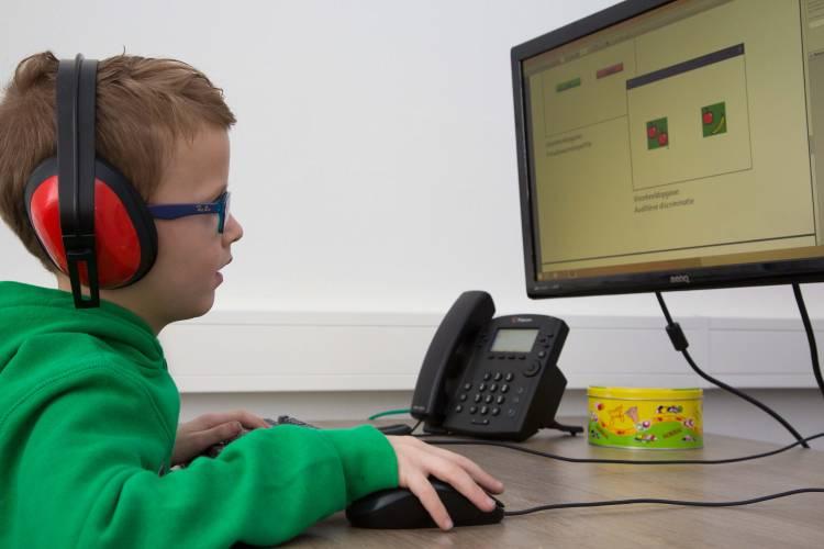 Jongen met hoofdtelefoon doet test die op een scherm wordt getoond