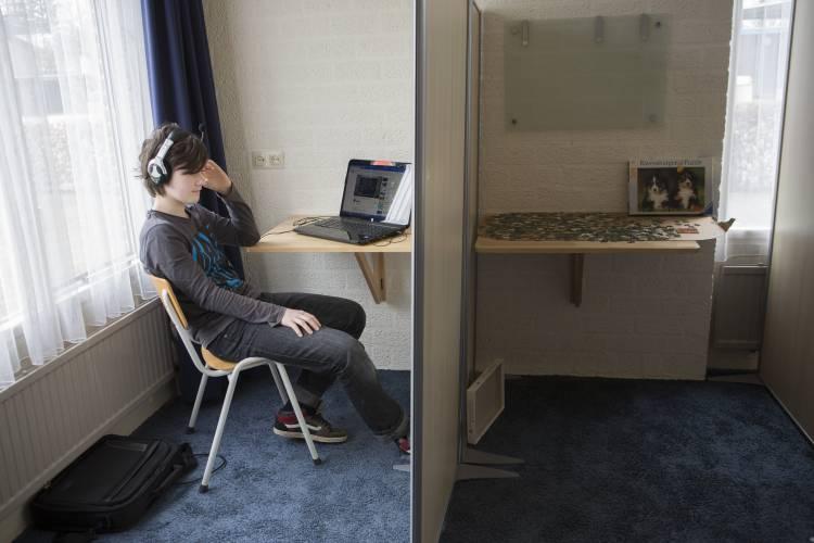 Jongere in afgescheiden ruimt met iPad