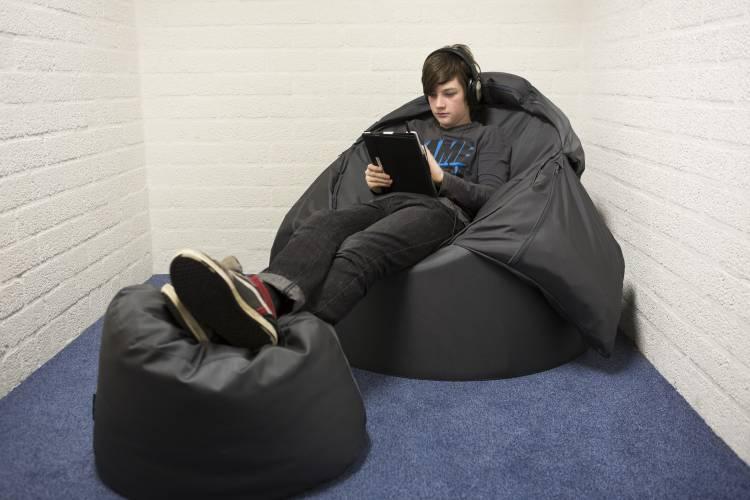 Jongere in zitzak, ontspannen lezend