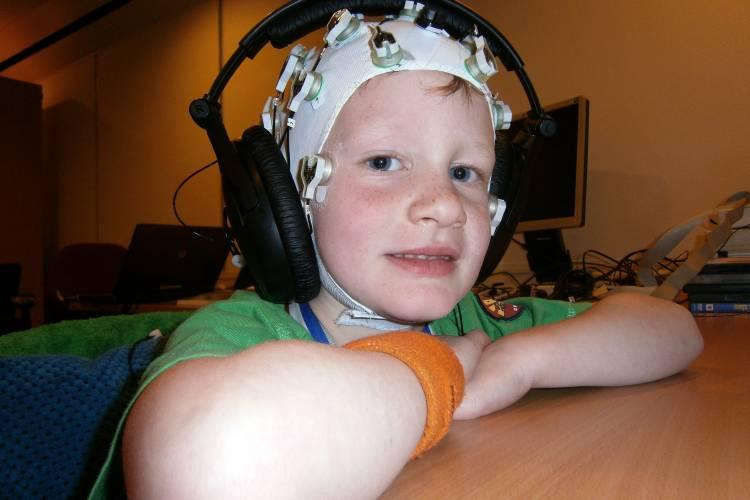 Jongen met EEG elektroden op het hoofd en koptelefoon