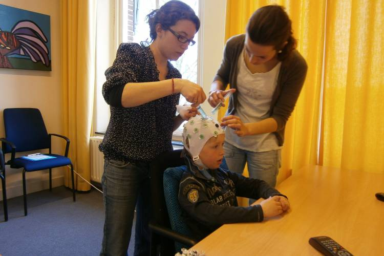 Twee volwassen vrouwen brengen EEG elektrodes aan bij een jongen