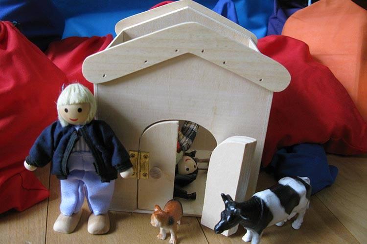 Houten huisje, boer en koe uit het spelmateriaal