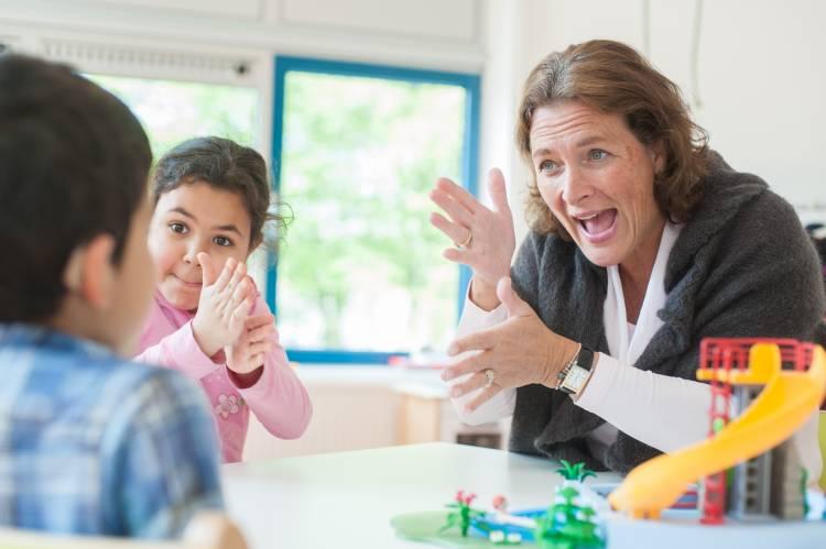 Gebarende leerkracht aan tafel met twee leerlingen