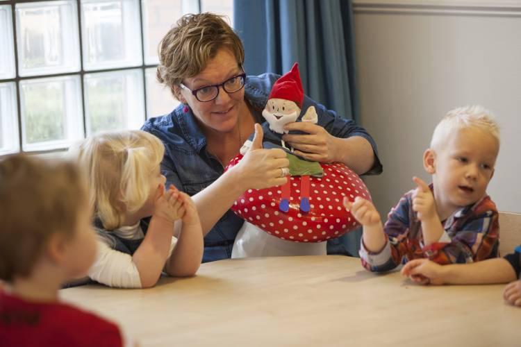 Begeleidster aan tafel met pop en drie jonge kinderen